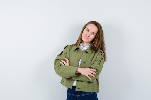 シャツを着た若い女性、腕を組んで立っているジャケット、自信を持って見える、正面図。