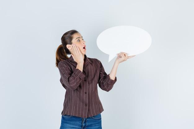 シャツを着た若い女性、頬に手のひらを持って、紙のポスターを保持し、ショックを受けて見えるジーンズ、正面図。