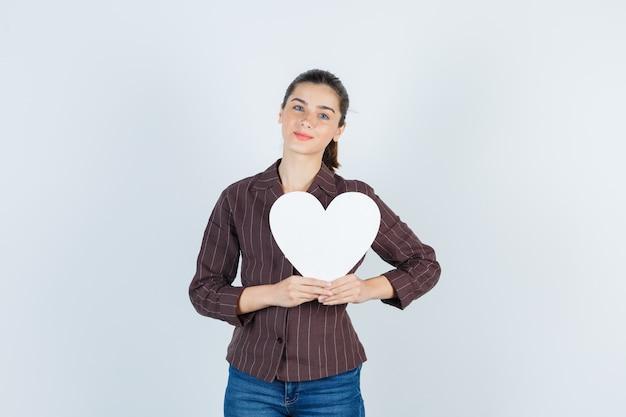 셔츠를 입은 젊은 여성, 청바지는 종이 포스터를 유지하고 사랑스러운 전면 전망을 보고 있습니다.