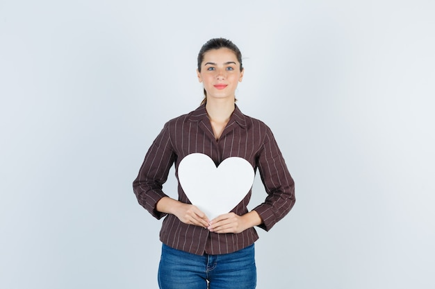 셔츠를 입은 젊은 여성, 종이 포스터를 유지하고 기쁘게 보이는 청바지, 전면 보기.
