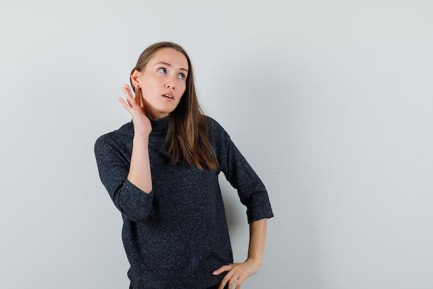 耳の後ろに手を保ち、好奇心旺盛に見えるシャツを着た若い女性