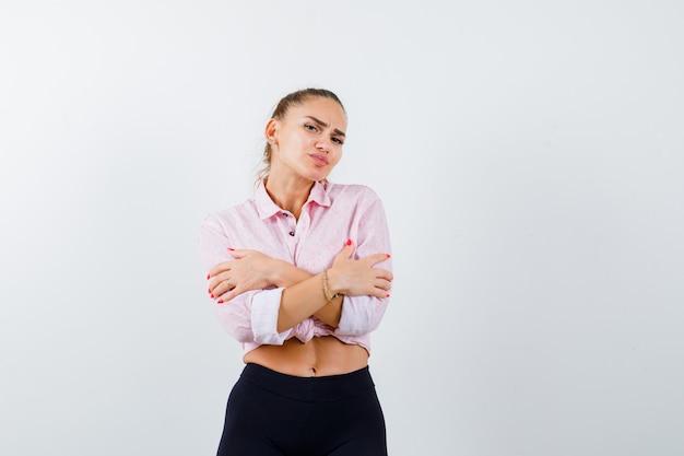 셔츠에 젊은 아가씨, 바지는 자신을 껴안거나 추위를 느끼고 무기력 한 모습을 보입니다.