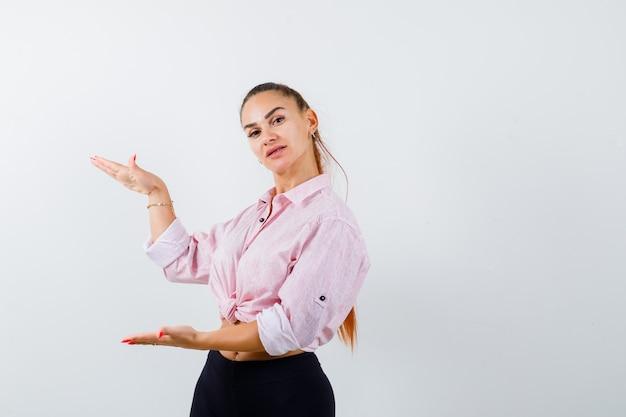 シャツを着た若い女性、大きなサイズのサインを示し、自信を持って見えるパンツ、正面図。