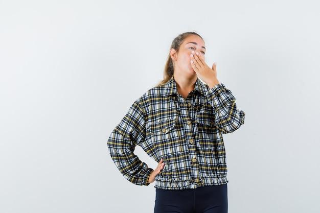 シャツを着た若い女性、あくびをしながら眠そうな顔をしている間、口に手をかざすショーツ、正面図。