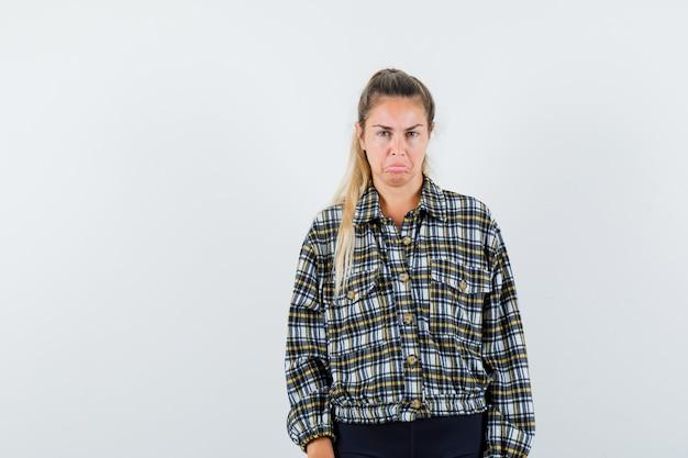 シャツを着た若い女性、カメラを見て悲しそうなショートパンツ、正面図。