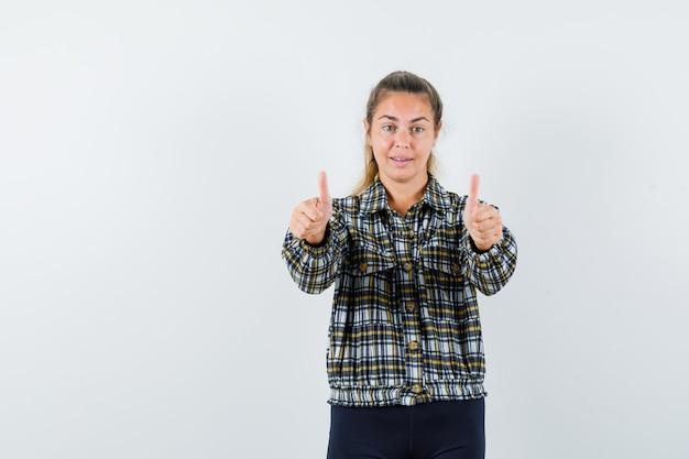 シャツを着た若い女性、二重の親指を上げて幸せそうに見えるショートパンツ、正面図。