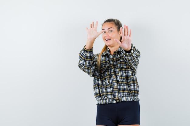 シャツを着た若い女性、停止ジェスチャーを示し、陽気に見えるショーツ、正面図。