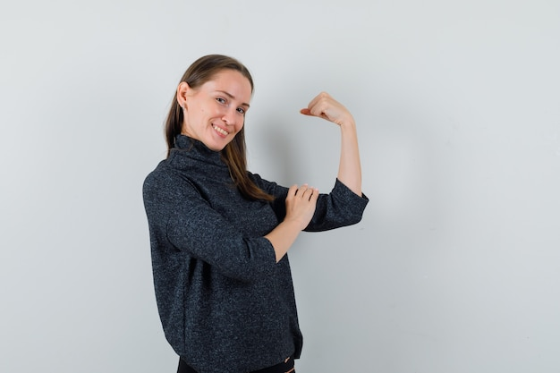 팔의 근육을 보여주는 셔츠에 젊은 아가씨와 자랑스럽게 찾고