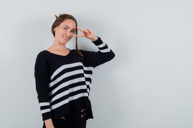 V 기호를 보여주는 유쾌한 찾고 셔츠에 젊은 아가씨