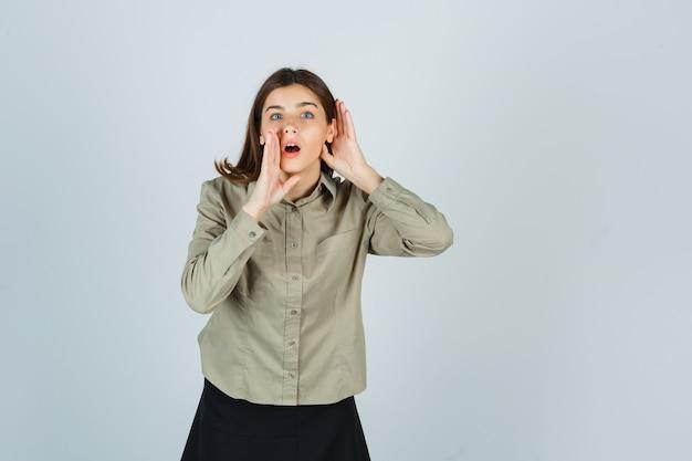 Девушка в рубашке, юбке, взявшись за руки за ухом и возле рта, чтобы рассказать секрет