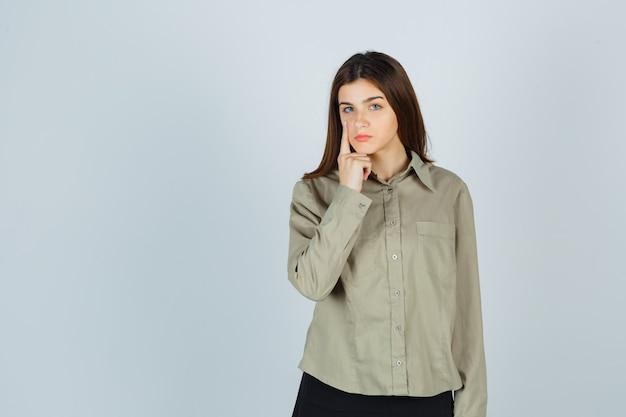 Молодая дама в рубашке, юбка, указывающая на ее веко и выглядящая усталой, вид спереди.