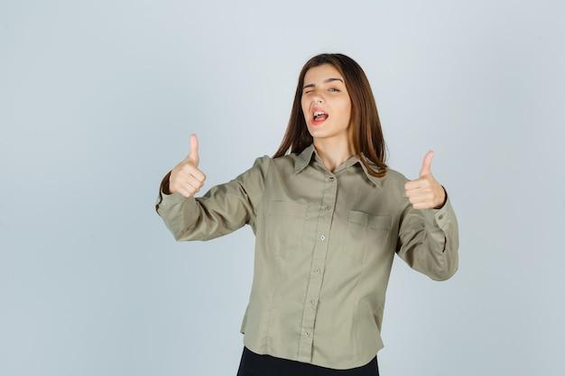 シャツを着た若い女性、まばたきと幸せそうに見える間、二重の親指を上に見せているスカート、正面図。