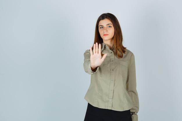 シャツを着た若い女性、停止ジェスチャーを示し、断固として見えるスカート、正面図。