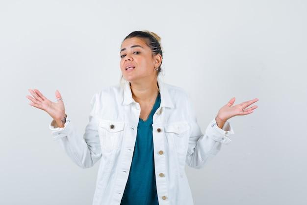 シャツを着た若い女性、腕を大きく広げて注意深く見ている白いジャケット、正面図。