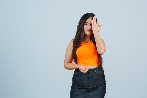 一重項の若い女性、手で目を覆い、魅力的に見えるミニスカート、正面図。