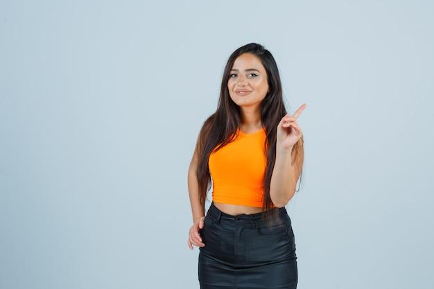 一重項の若い女性、上向きできれいに見えるミニスカート、正面図。