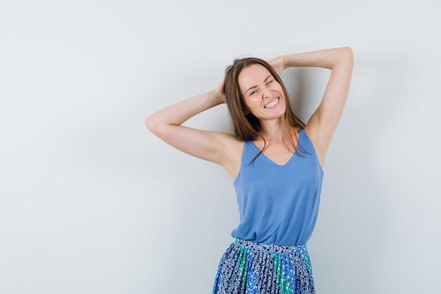 一重項の若い女性、頭の後ろで手を握り、リラックスして見えるスカート、正面図。