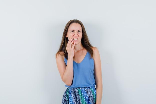 一重項の若い女性、歯痛に苦しんでいて不快に見えるスカート