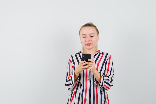 彼女の電話をチェックしている縞模様のブラウスの若い女性