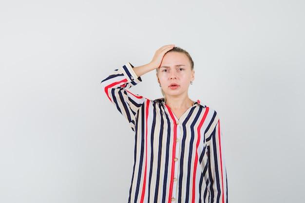 Девушка в полосатой рубашке держит руку за голову и смотрит вниз