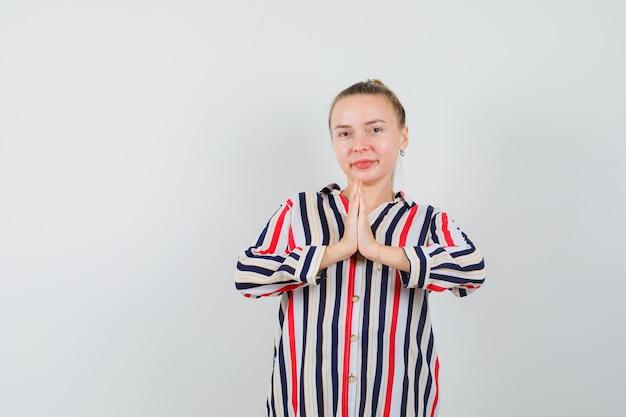 ナマステのジェスチャーを示し、陽気に見える縞模様のシャツの若い女性