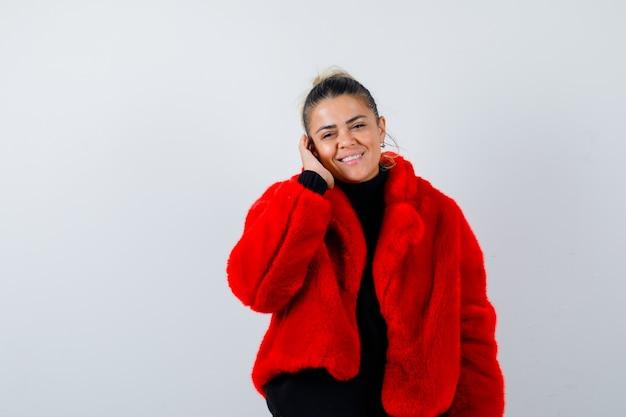 セーターの若い女性、耳に手と陽気に見える毛皮のコート、正面図。