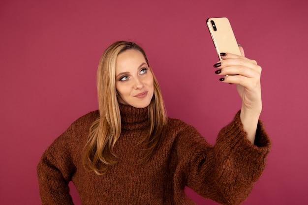 ピンクのスタジオで電話でセルフ写真を作るセーターの若い女性。
