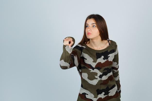 離れてポーズをとって注意深く見てセーターの若い女性