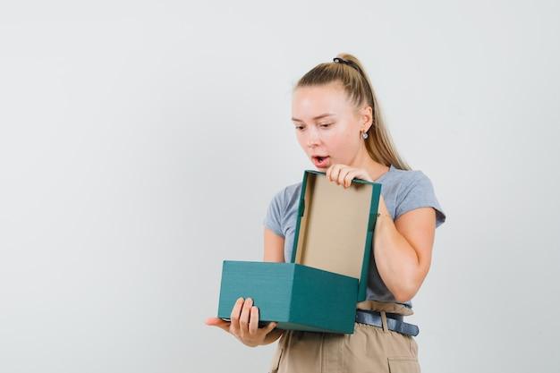 Tシャツとズボンの若い女性がプレゼントボックスを見て驚いて見える