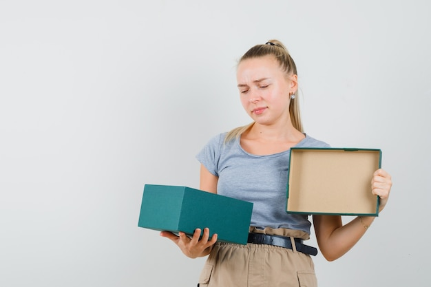 Tシャツとズボンの若い女性がプレゼントボックスを見てがっかりしている