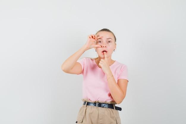 입술에 손가락을 잡고 손가락을 통해 찾고 티셔츠와 바지에 젊은 아가씨