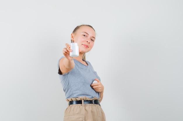 T- 셔츠와 바지에 약 병을 표시 하 고 자신감을 찾고 젊은 아가씨