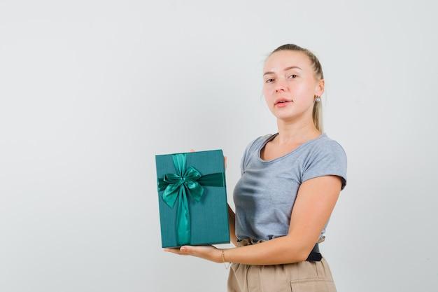 プレゼントボックスを見せて自信を持って見えるtシャツとパンツの若い女性