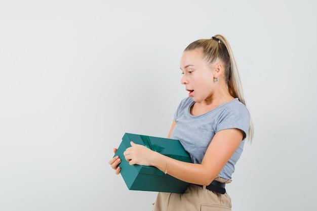 Tシャツとズボンの若い女性がプレゼントボックスを開こうとして好奇心旺盛に見える、
