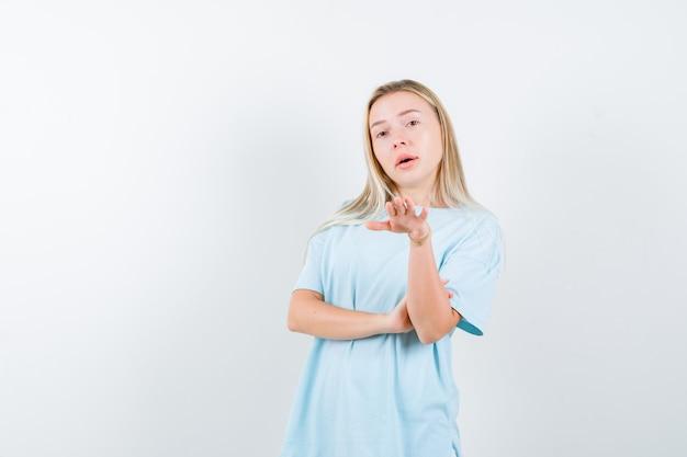 誰かを前に招き、自信を持って、正面図を探しているtシャツの若い女性。