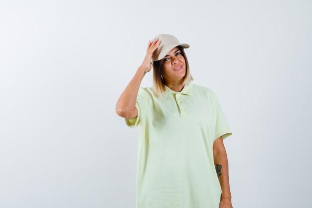 T- 셔츠에 젊은 아가씨, 모자 포즈와 자신감, 전면보기를 찾고있는 동안 모자에 손을 잡고.
