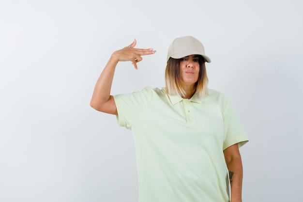 Tシャツを着た若い女性、自殺ジェスチャーをし、絶望的に見えるキャップ、正面図。