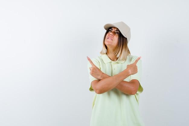 Молодая дама в футболке, кепка, направленная вверх и задумчивая, вид спереди.
