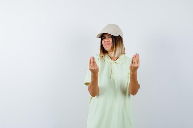 T- 셔츠에 젊은 아가씨, 이탈리아 제스처를 보여주는 모자와 기쁘게 찾고, 전면보기.