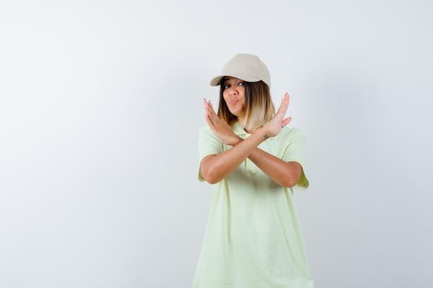 Tシャツを着た若い女性、唇をふくれっ面と自信を持って見ながら停止ジェスチャーを示すキャップ、正面図。