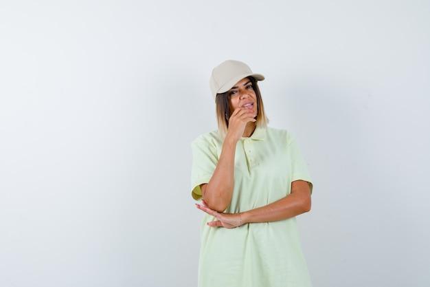 T- 셔츠에 젊은 아가씨, 생각 포즈에 서 있고 잠겨있는, 전면보기를 찾고 모자.
