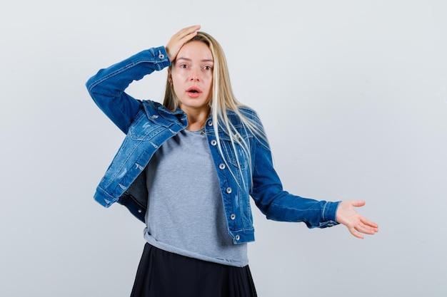 T- 셔츠, 데님 재킷, 치마에 머리에 손을 잡고 무기력 한 젊은 아가씨