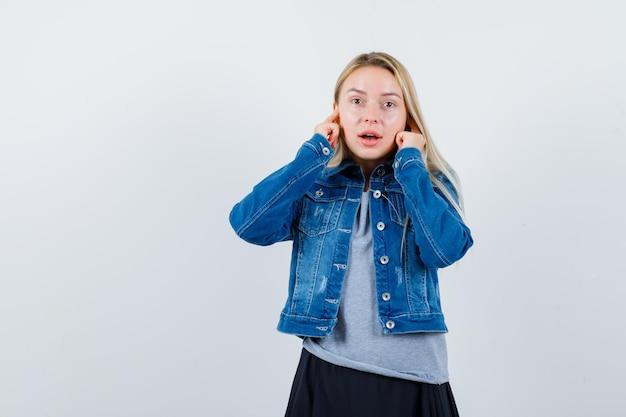T- 셔츠, 데님 재킷, 손가락으로 귀를 막고 짜증이 나는 치마에 젊은 아가씨