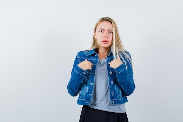 티셔츠, 데님 재킷, 치마를 입은 젊은 아가씨가 자신을 가리키며 놀랍습니다.