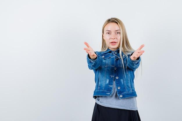 T- 셔츠, 데님 재킷, 제스처를주고 화려한 보이는 치마에 젊은 아가씨