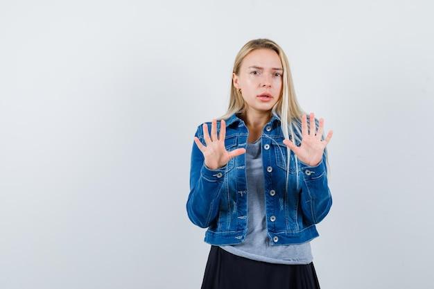 T- 셔츠, 데님 재킷, 치마에 손바닥을 보여주는 젊은 아가씨와 자신감을 찾고