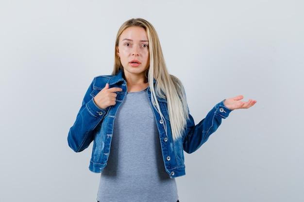 Tシャツ、デニムジャケット、スカートのストレッチで手を伸ばしてジェスチャーを質問し、物思いにふける若い女性