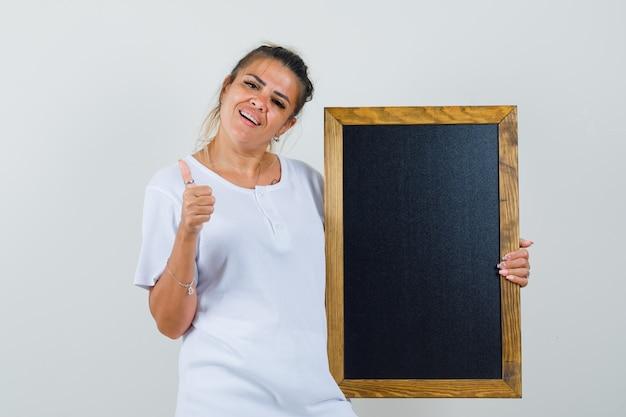 엄지 손가락을 보여주는 칠판을 들고 쾌활한 찾고 티셔츠에 젊은 아가씨