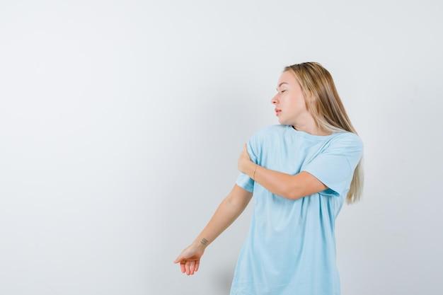 腕に手を握り、思慮深く孤立しているように見えるtシャツの若い女性