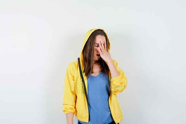 Молодая дама в футболке держит руку на лице и смотрит забывчиво, вид спереди.